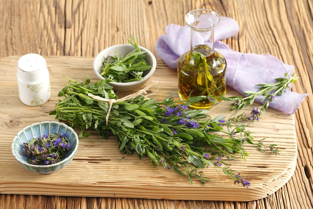 Fresh hyssop and olive oil infused with hyssop on a chopping board