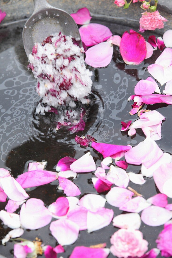 Rose bath salts being poured into water