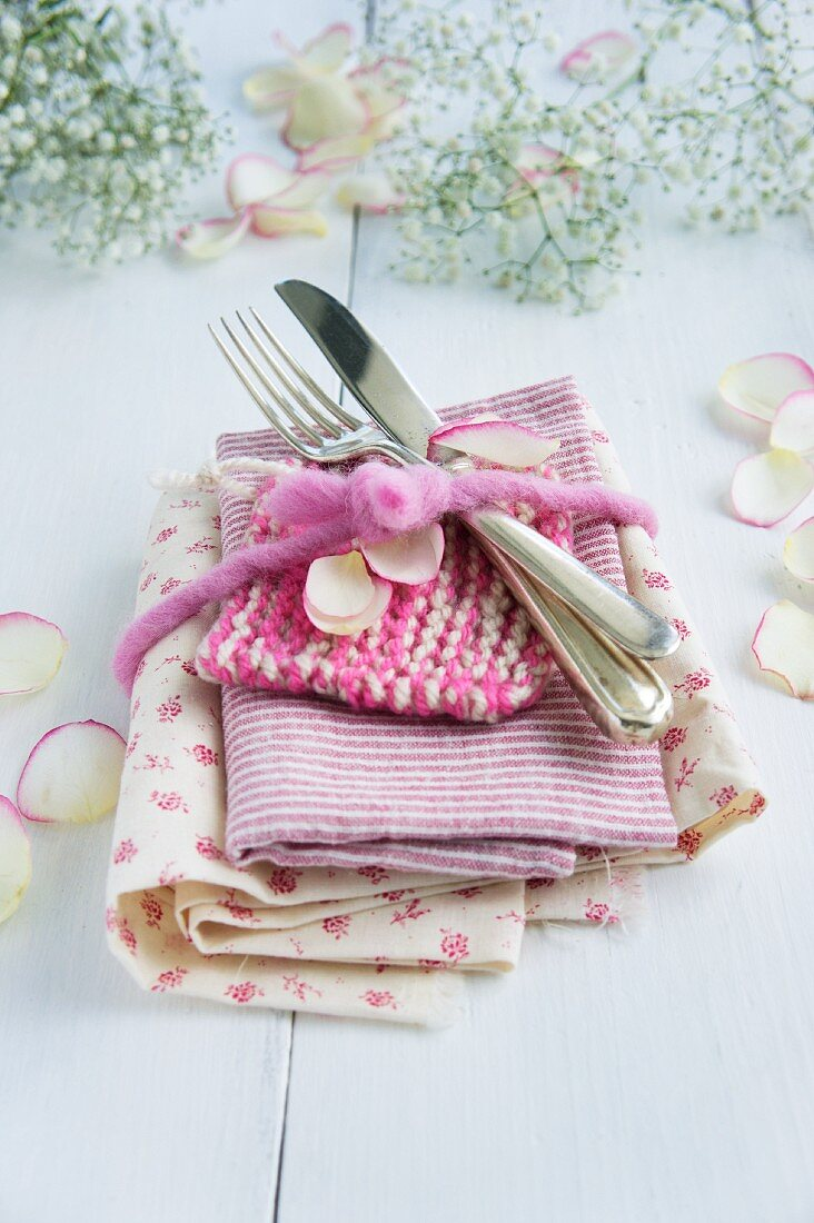 Stack of floral and striped fabrics and cutlery tied with a felt ribbon and scattered with petals