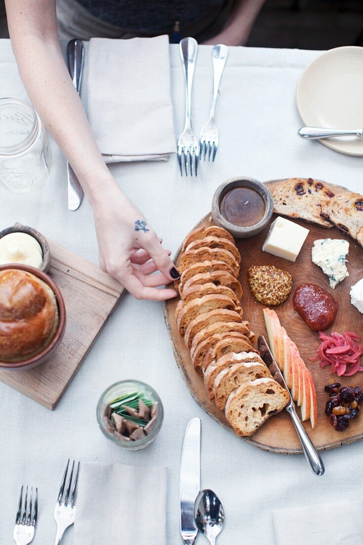 A cheese platter with a rustic baguette