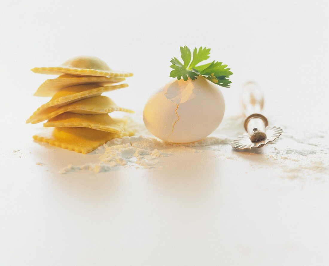 A still life featuring tortellini, flour, an egg and a pastry cutter