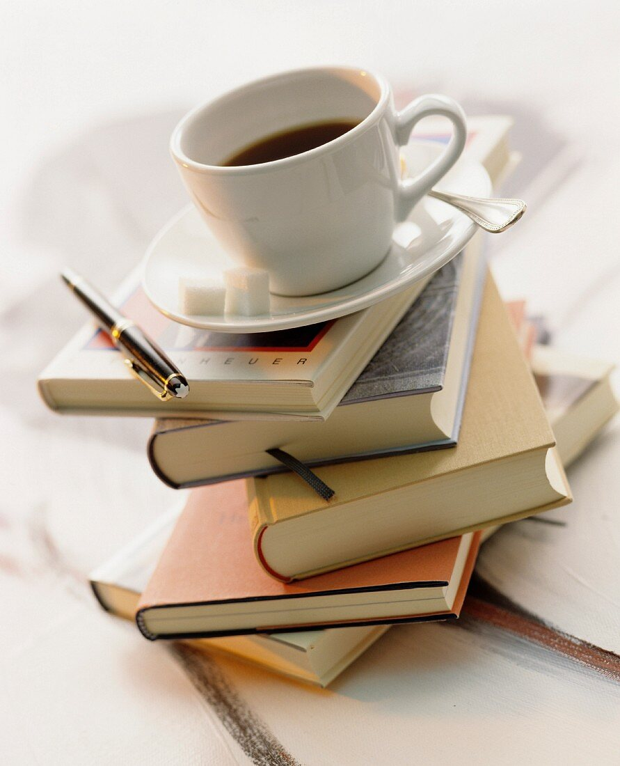 A cup of coffee on top of a stack of books
