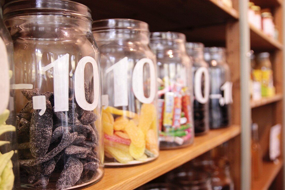 Assorted sweets in open storage jars, labelled with price per item, on wooden shelving