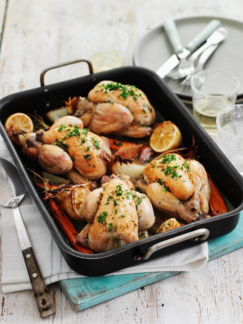 Roast spring chickens with lemons, onions and sliced peppers