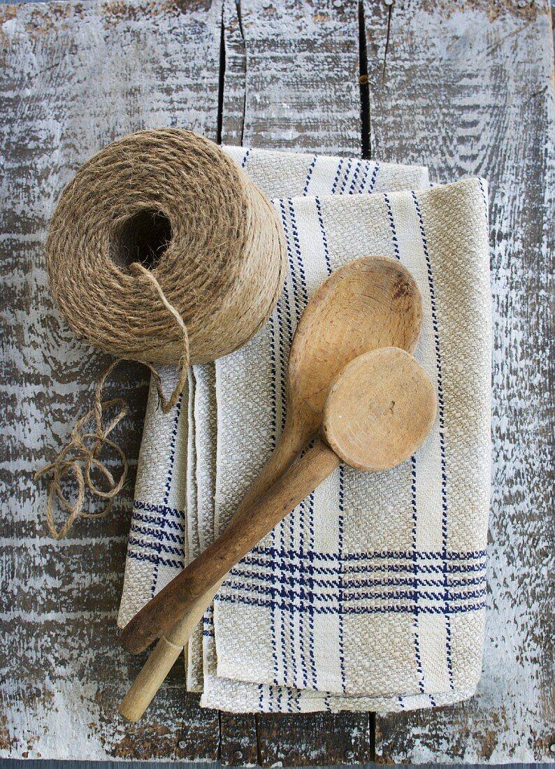 Rustic kitchen utensils: linen dish towel, twine and wooden spoon