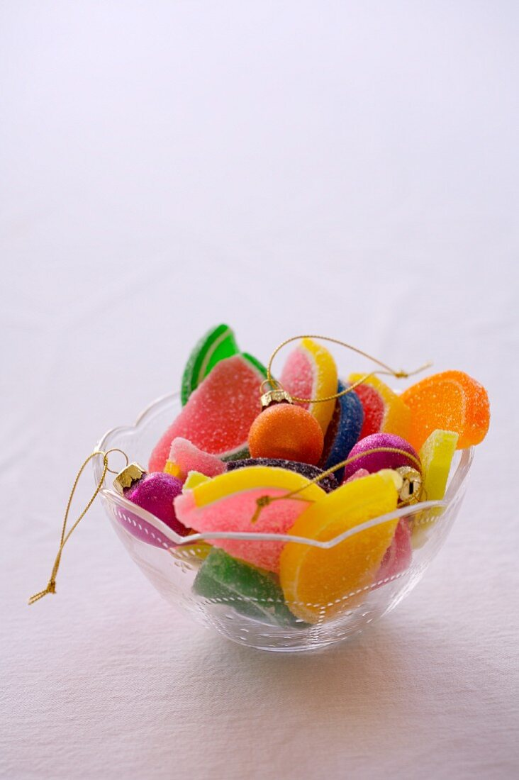 A Glass Bowl with Christmas Ornaments and Jelly Fruit Candy