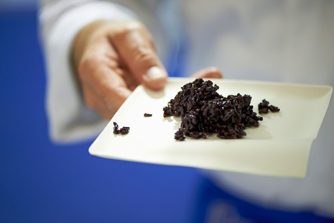 Man holding a plate with riso venere (black rice, Italian)