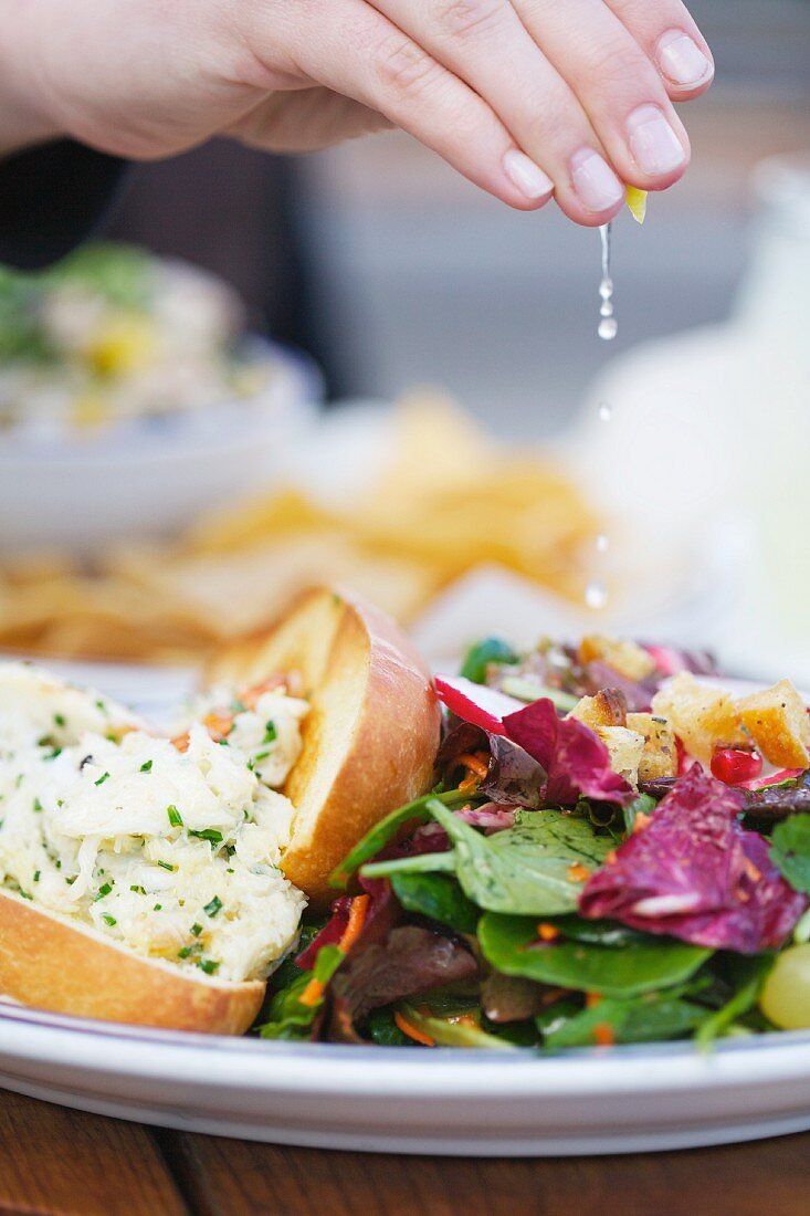 Squeezing Lemon Over a Lobster Roll and a Side Salad