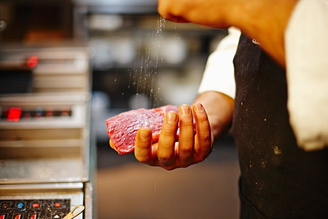A chef seasoning beef steak with salt