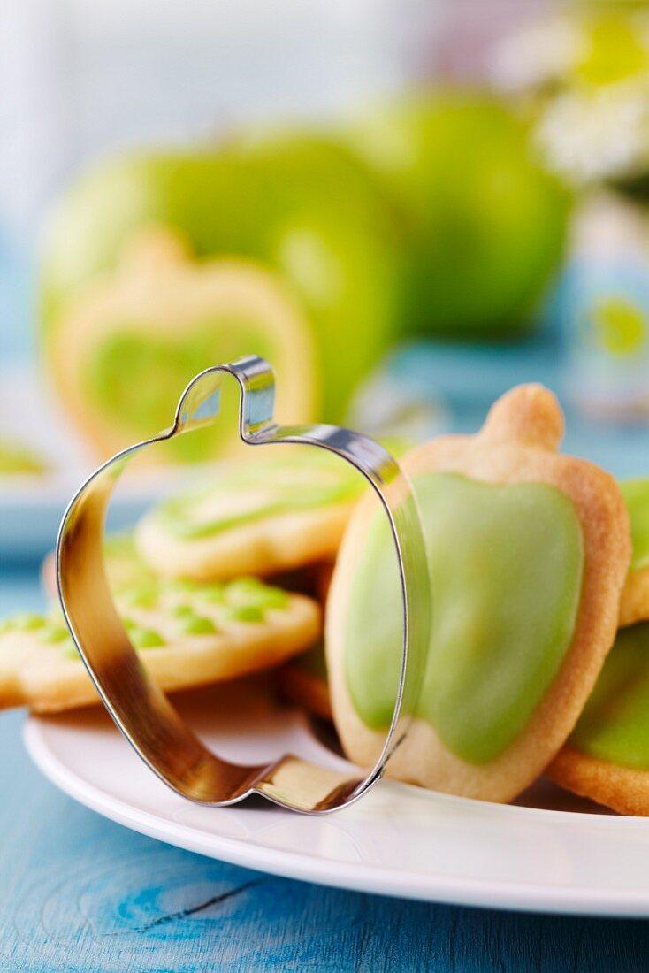 Keksausstecher in Apfelform auf Teller mit Keksen