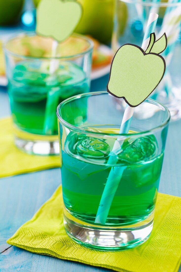 Glasses of sweet woodruff pop with drinking straws decorated with cut-out paper apples