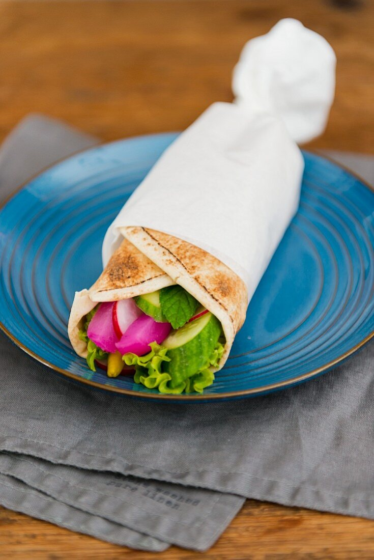 Vegetarian wrap with cucumber, salad leaves, peppermint, pickled radish and fresh radish