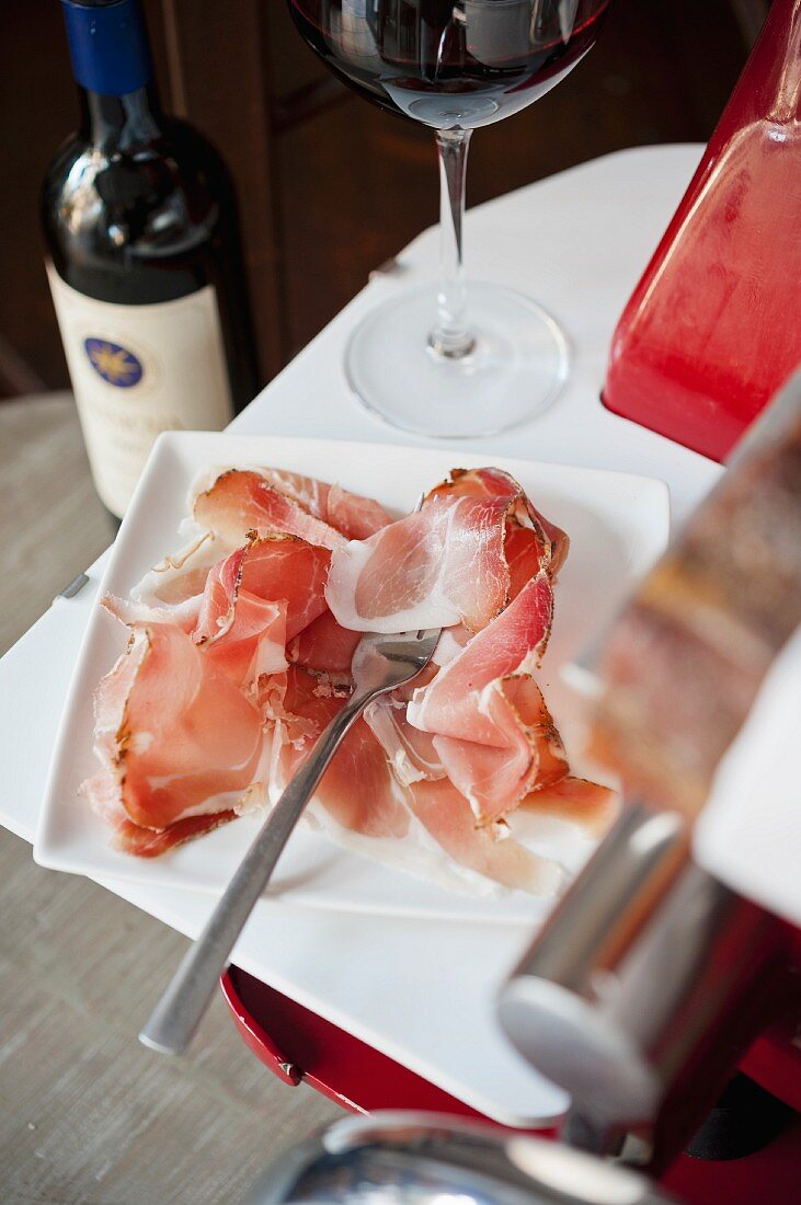 Prosciutto, cut into wafer thin slices, on a slicing machine