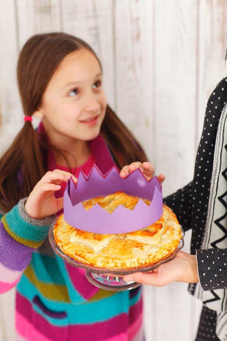 A girl placing a paper crown on a Galette des Rois