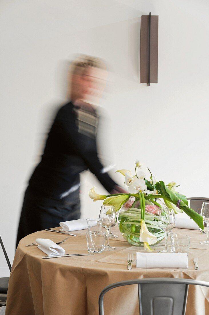 Frau arrangiert Blumen auf einem Restauranttisch