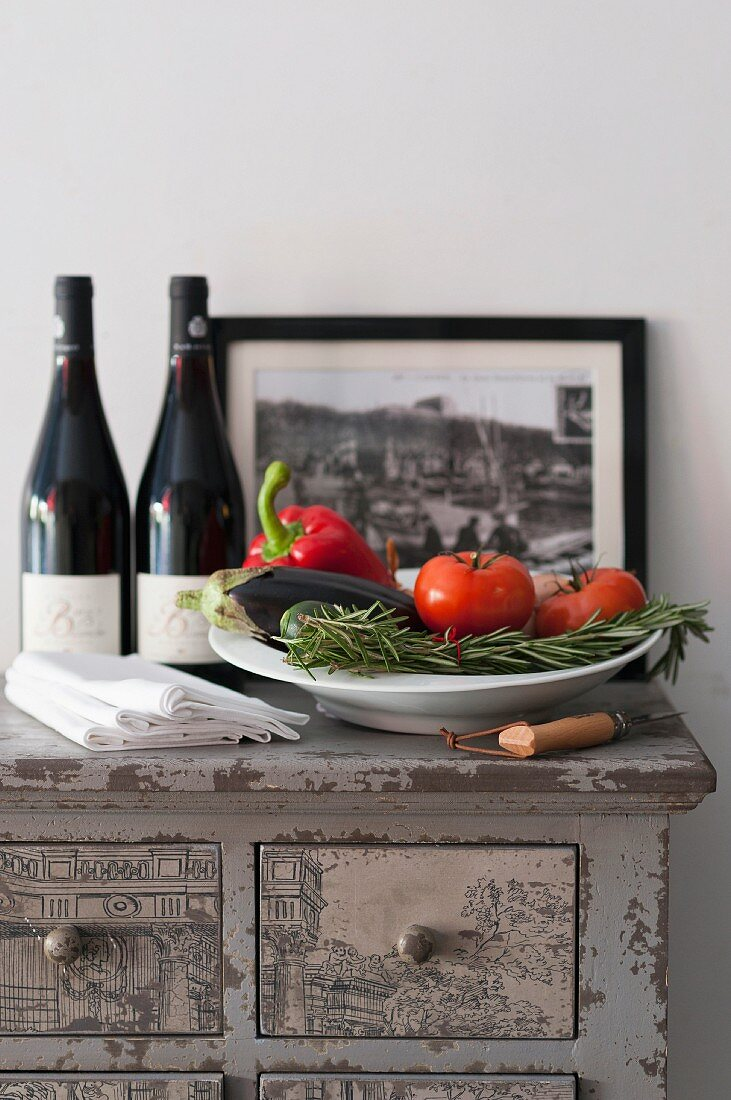 A plate of vegetables with rosemary, bottles of red wine and napkins on a chest of drawers