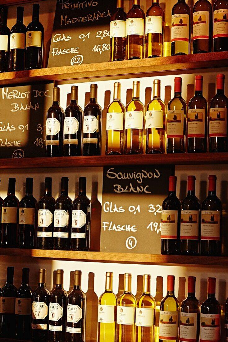 Assorted bottles of wine on shelves in a restaurant