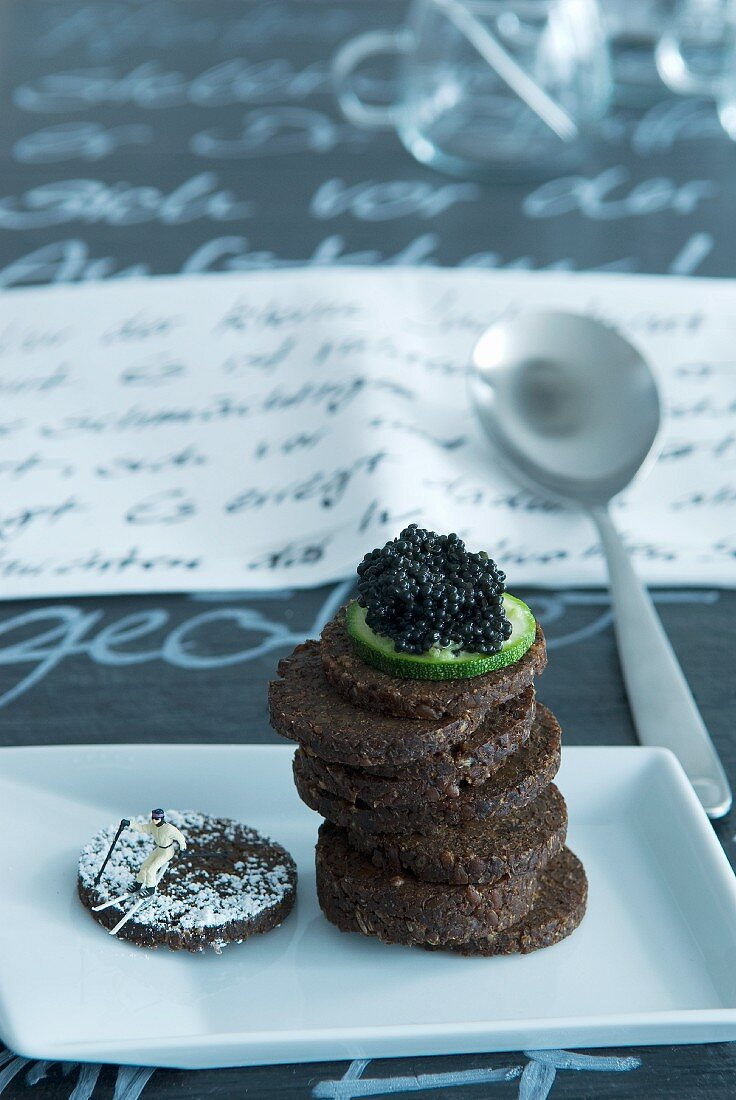 A stack of pumpernickel topped with a slice of cucumber and caviar next to a model skier