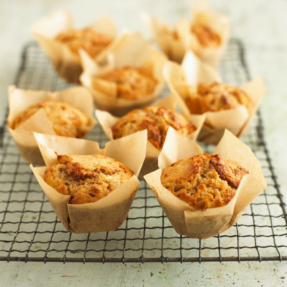 Several apple & walnut muffins in baking parchment on a wire rack