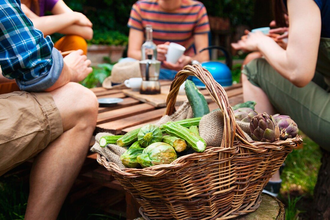 A basket of fresh vegetables, in the background a group of young people