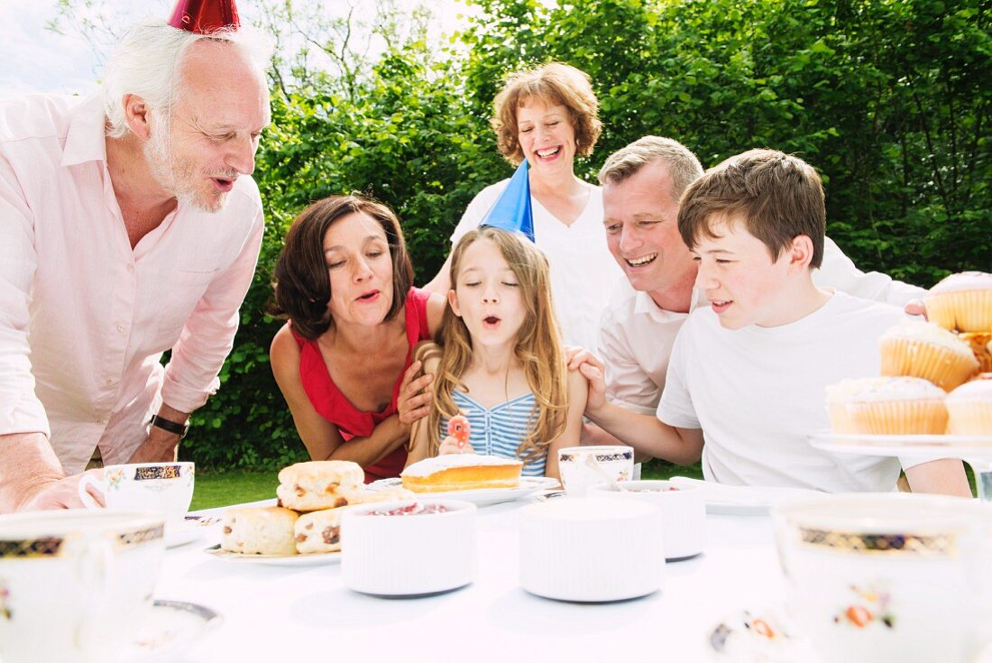 Family celebrating a birthday in the garden