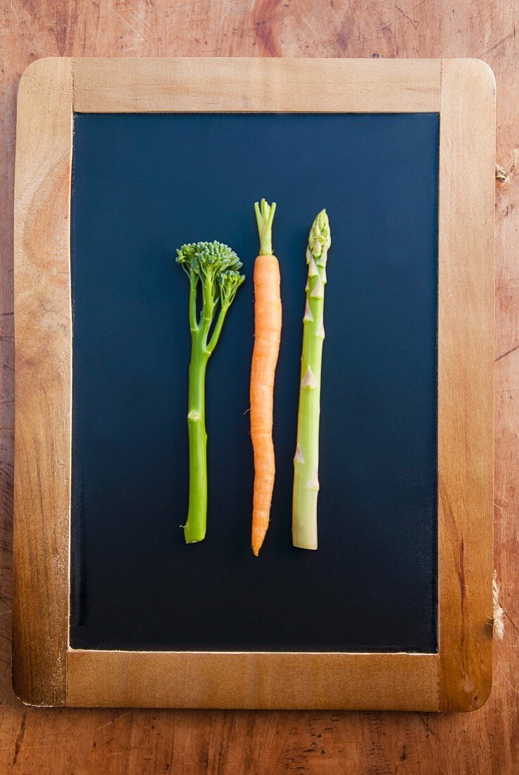 A stem of broccoli, a carrot and a stalk of asparagus lying on a blackboard