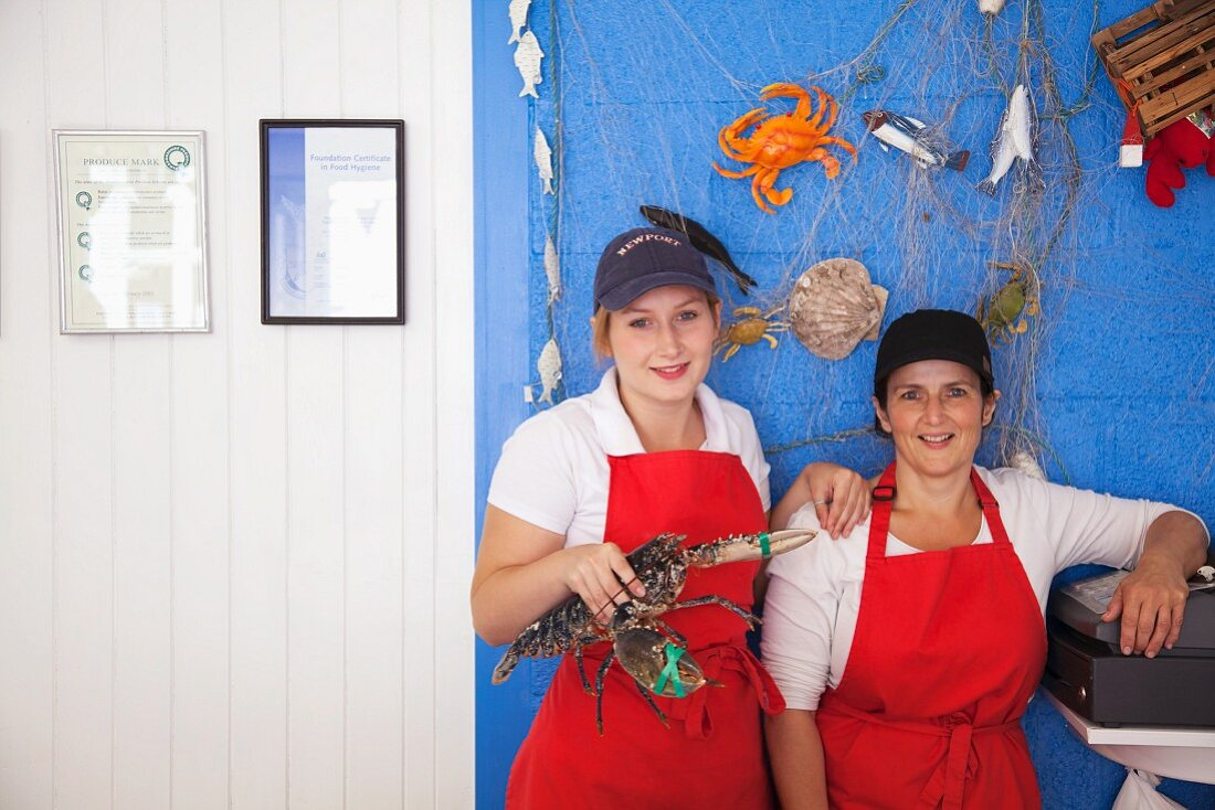 Two shop assistants holding a fresh lobster