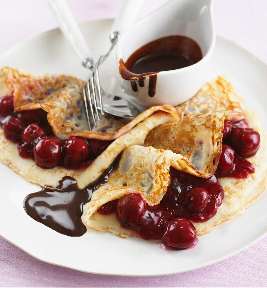 Pancakes with cherries and chocolate sauce