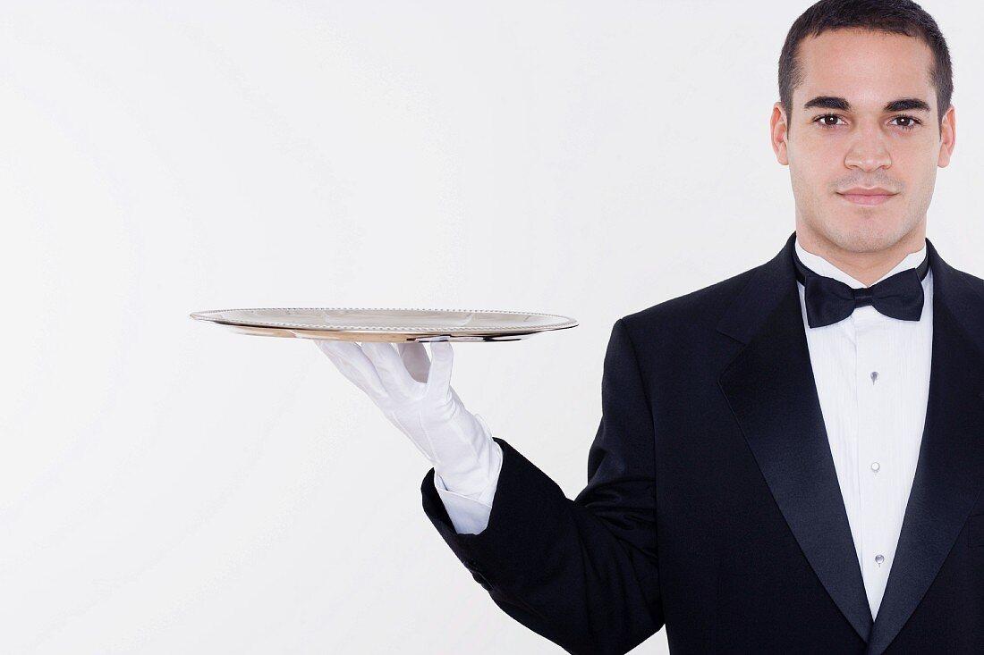 Portrait of male waiter balancing tray