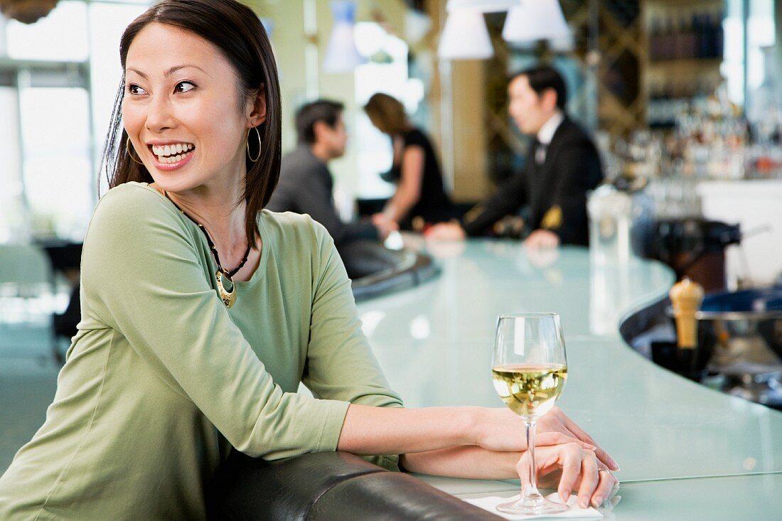 Woman at bar with glass of wine
