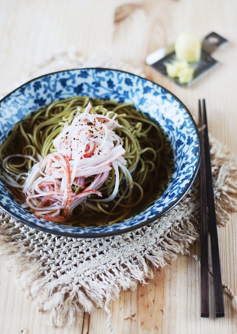 Cha Soba (buckwheat noodles with green tea) in broth, garnished with surimi strips