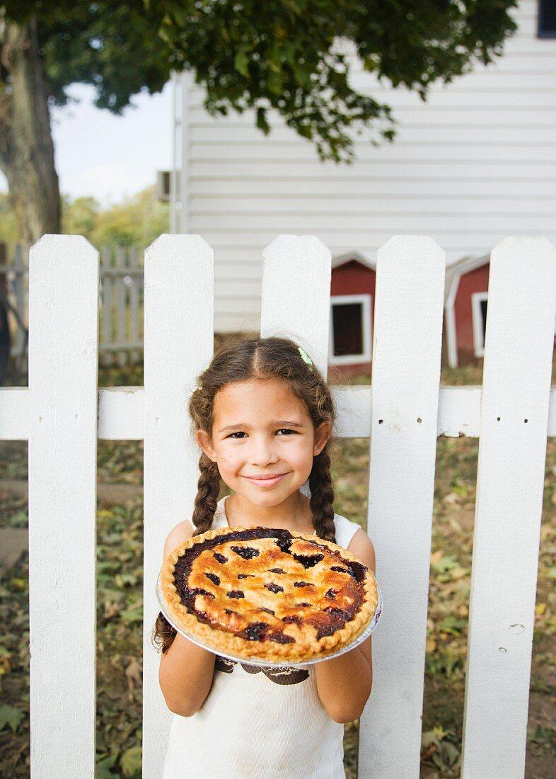 Hispanic girl holding homemade pie