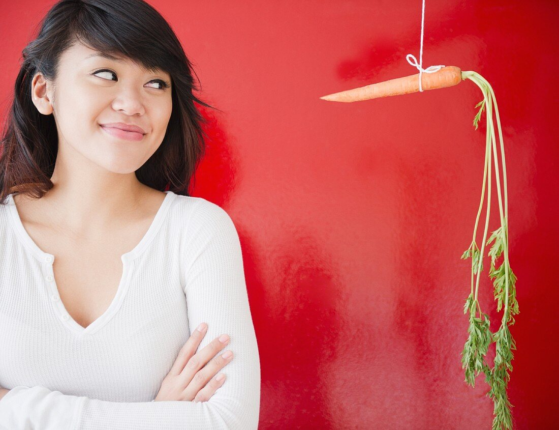 Pacific Islander woman looking at a carrot on a string