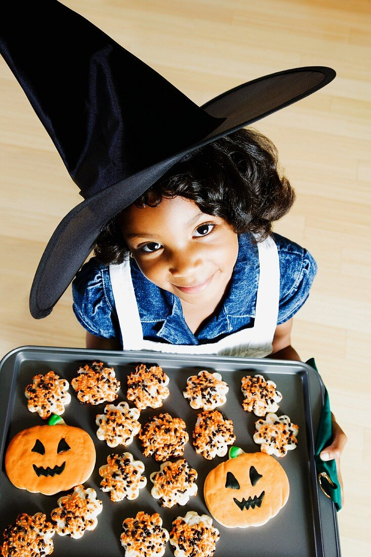 A little witch with Halloween biscuits