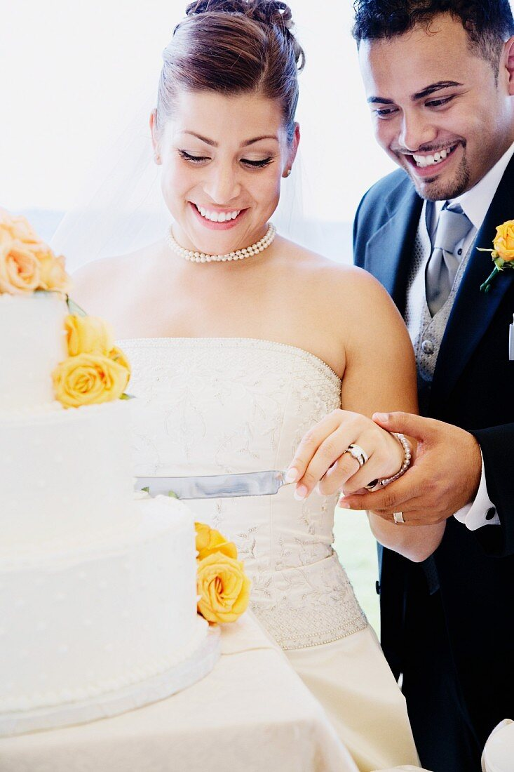 Multi-ethnic bride and groom cutting cake