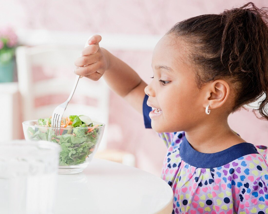 African girl eating salad