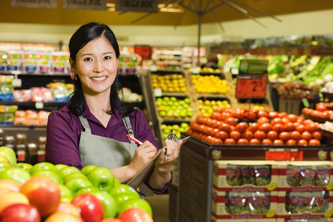 Asian woman working in produce section of grocery store