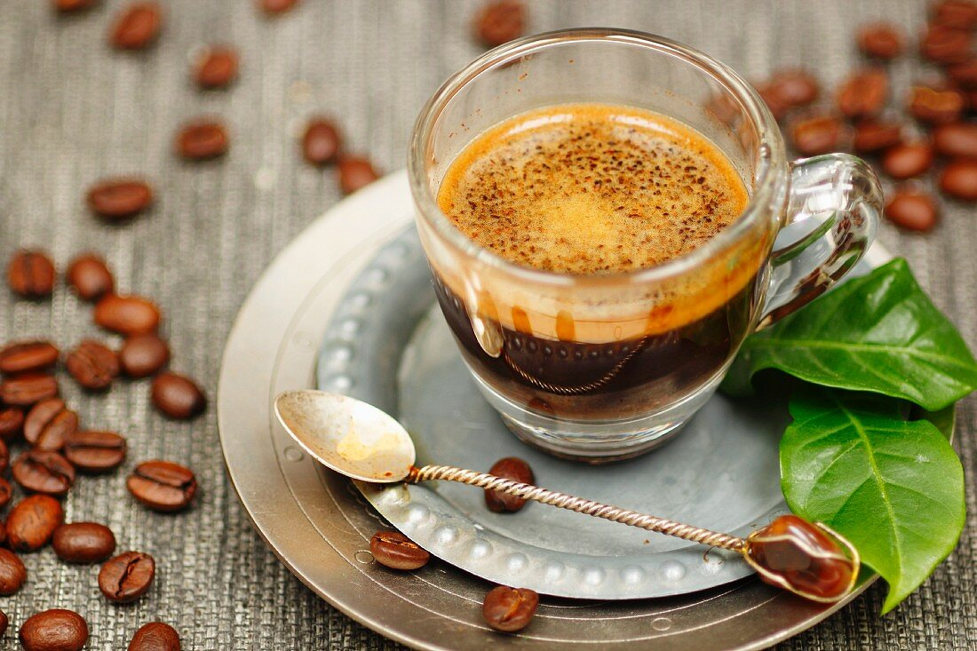 Espresso in a glass with coffee leaves and coffee beans