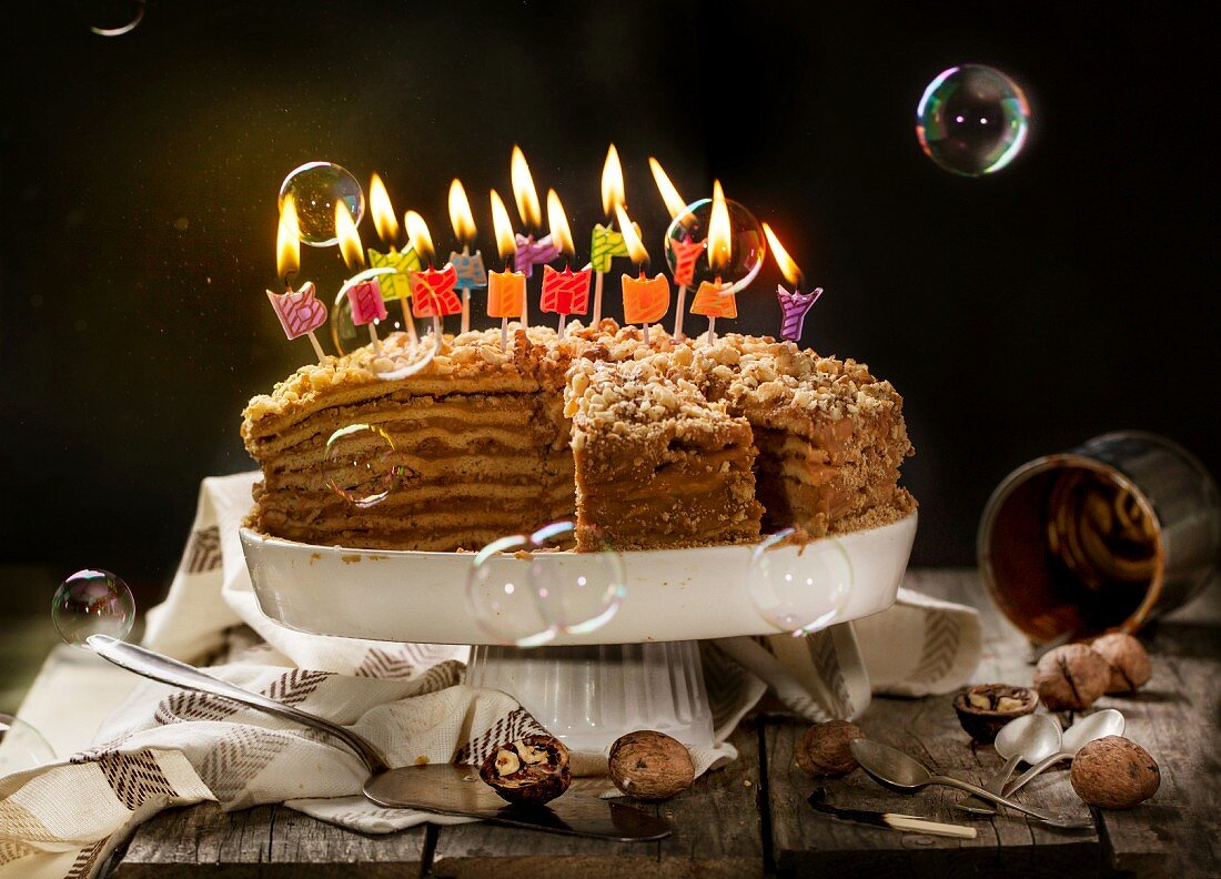 Birthday honey cake with walnuts with burning candles and soap bubbles
