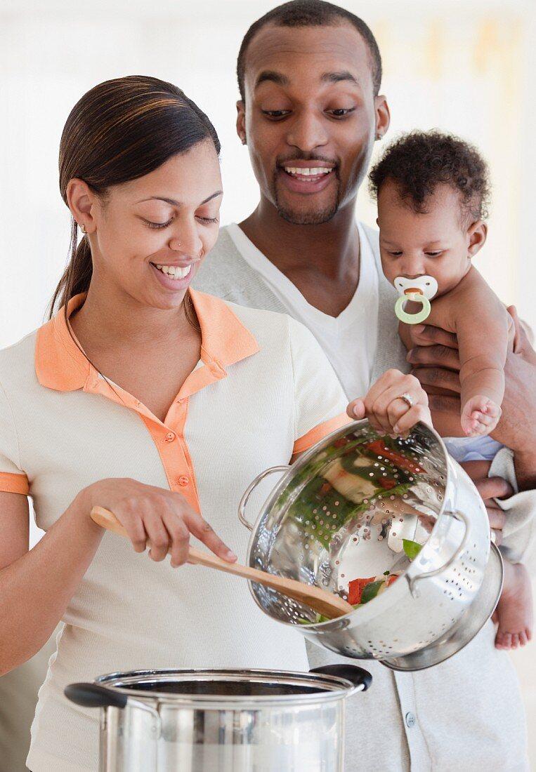 Junge Familie, eine Gemüsesuppe kochend