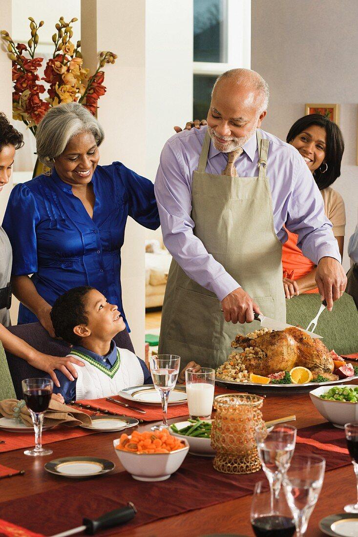 African American man carving Thanksgiving turkey