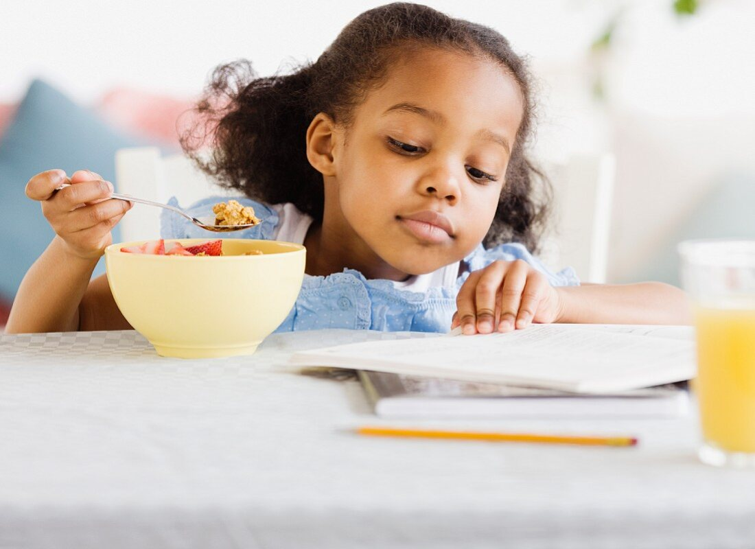 Mixed race girl reading and eating breakfast