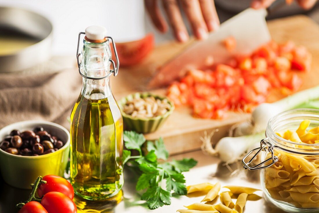 Olive oil and ingredients for a pasta dish; tomatoes are being finely chopped in the background