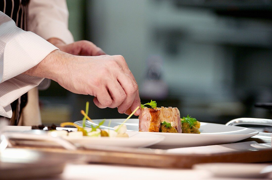 Chef plating up pork dish during service at working restaurant