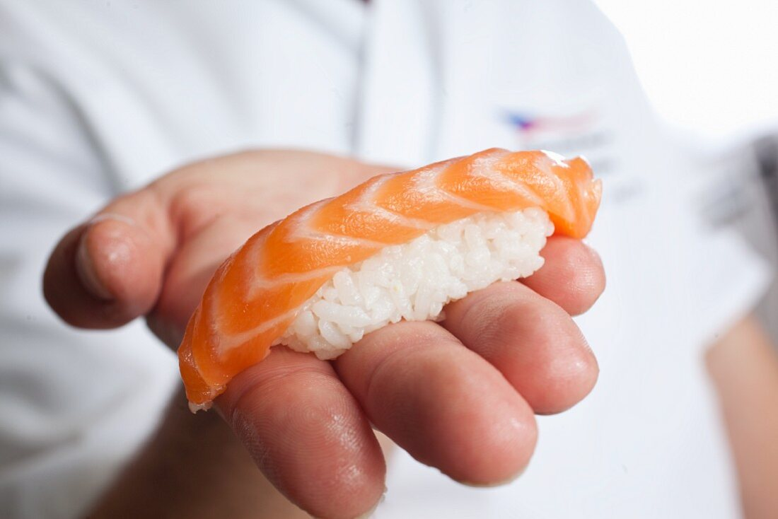 A chef holding a piece of nigiri sushi with salmon
