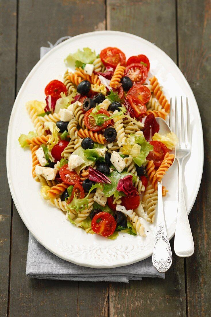 Pasta salad with olives, cherry tomatoes, iceberg lettuce and mozzarella