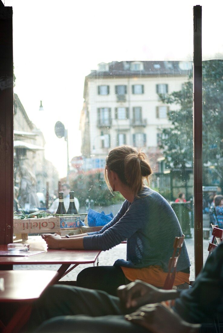 Woman Sitting at Cafe Table, Italy