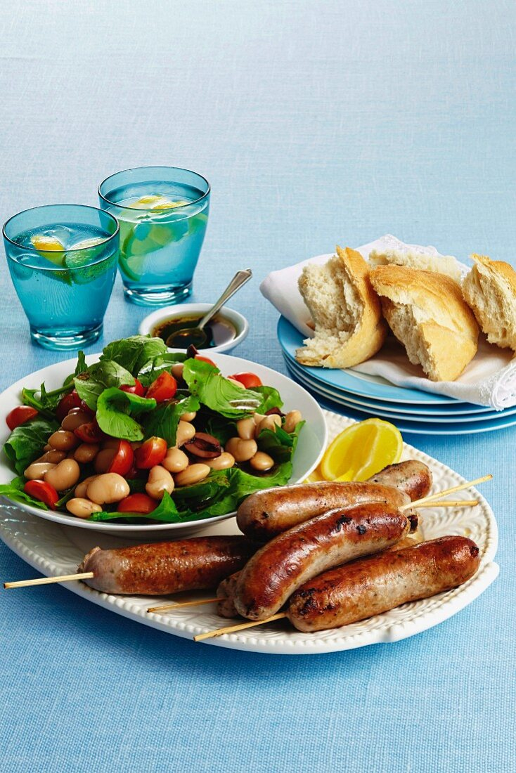 Skewered sausages with a bean and olive salad