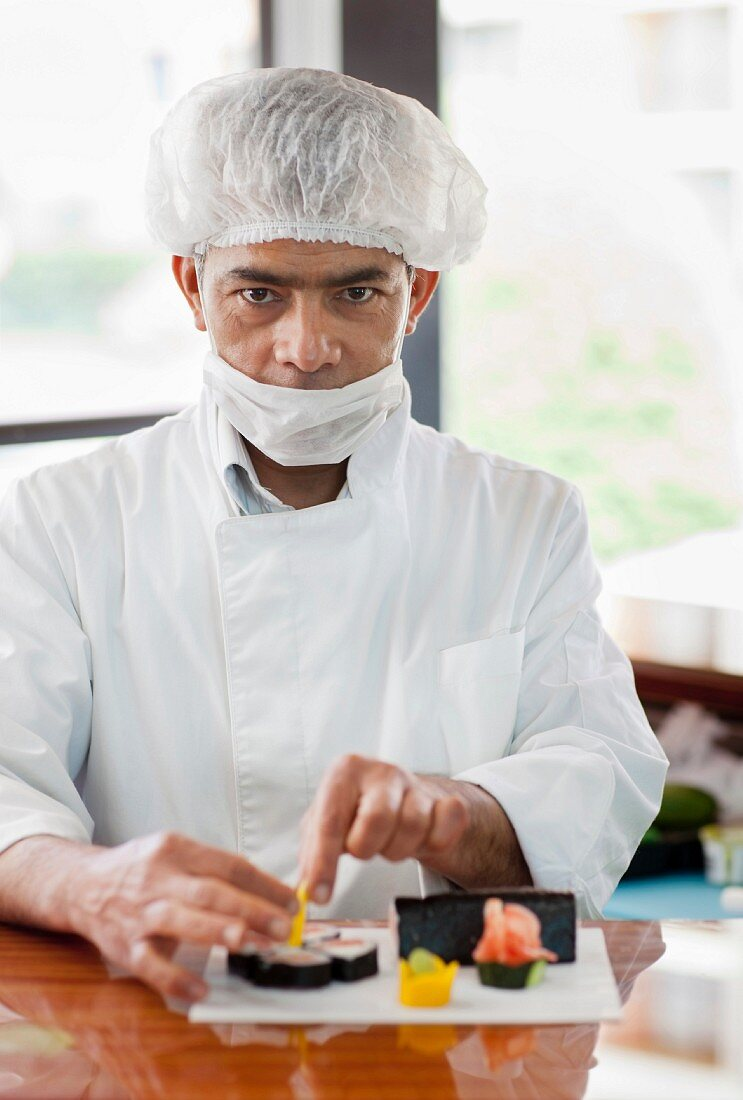 A chef wearing a mouth protection preparing sushi