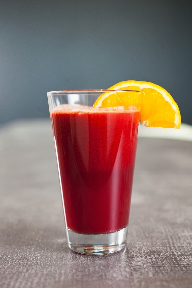 A cocktail made out of fresh vegetable and fruit - juice / tomato, orange and beetroot